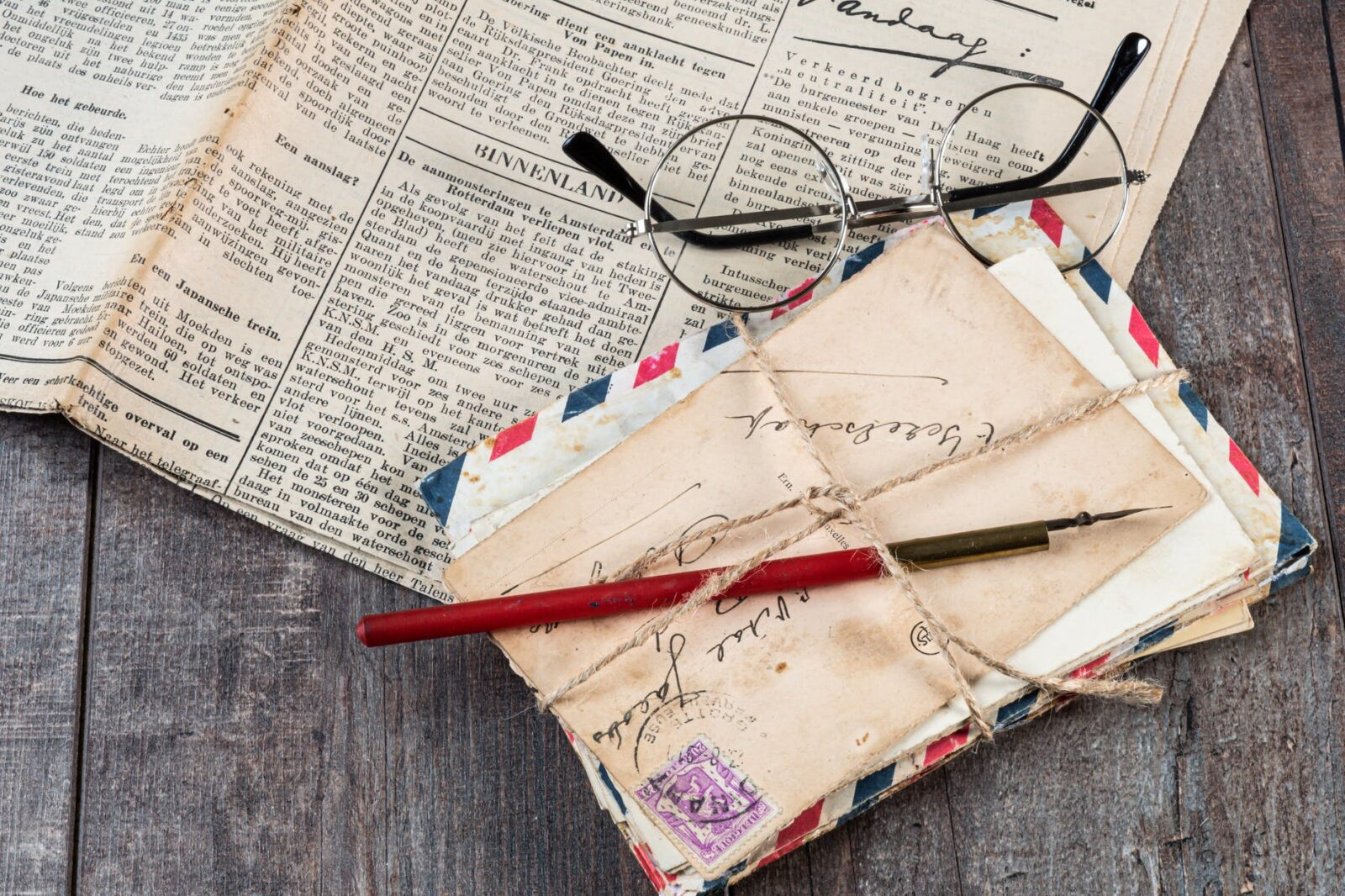 eyeglasses on newspaper beside mail envelops